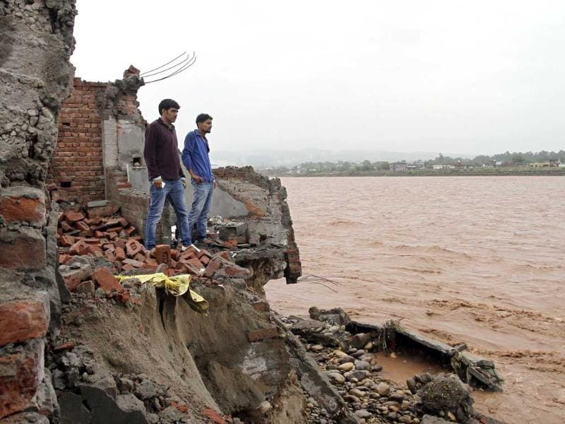 Onlookers stand on the debris of a house that was damaged by floodwaters on the banks of the river Tawi after heavy rains in Jammu. (Reuters)