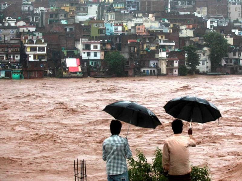 Indian residents look on towards threatened houses as waters from the overflowing Tawi river rage past in Jammu. (AFP Photo)