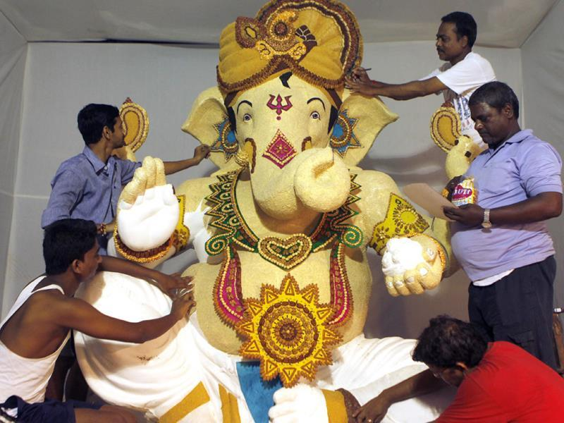 Tulsi Building Shree Ganeshotsav Mandal's Malekar and Mohite family members give final touch to the Ganesh idol by using 13 different items: til, peanut, hazelnut, almond, lavang, etc in Mumbai. (Anshuman Poyrekar/HT photo)