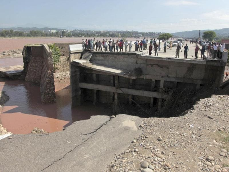 People look at a bridge across the Tawi River that was damaged in the floods at Mandal village on the outskirts of Jammu.(AP Photo)