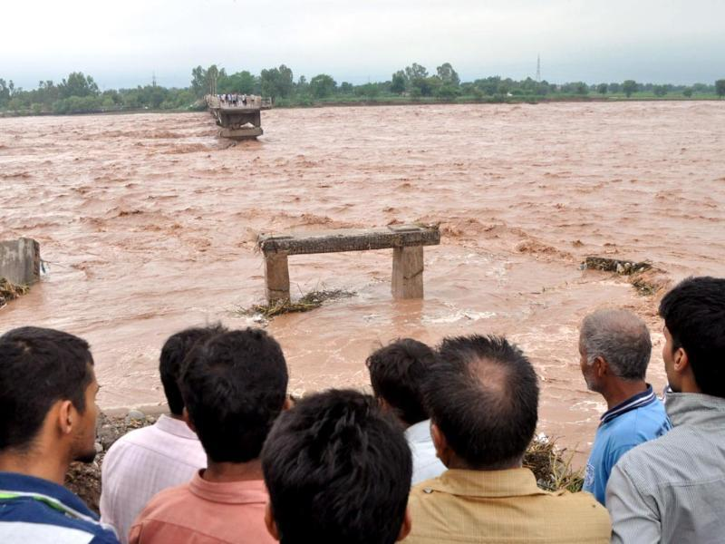 Indian villagers look on at a missing section of a bridge across the overflowing Tawi river that was swept away as flooding continues in the Mandal area of Jammu. (AFP Photo)
