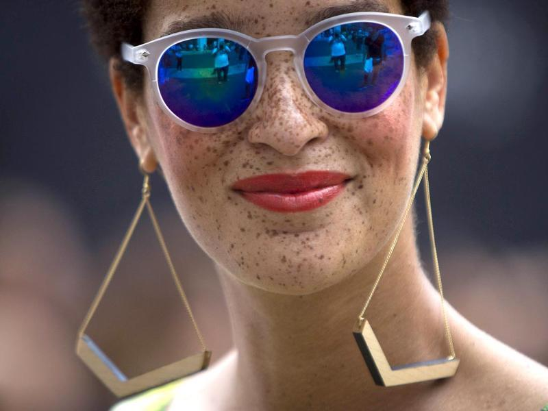 A fashionista wearing sunglasses smiles as she walks around Lincoln Center during New York Fashion Week in the Manhattan borough of New York. (Reuters Photo)