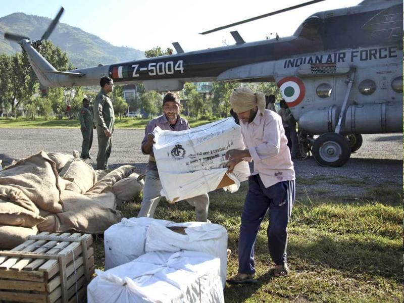 Laborers carry relief material for flood-affected victims in Poonch, around 276 kilometers (166 miles) from Jammu. (AP Photo)