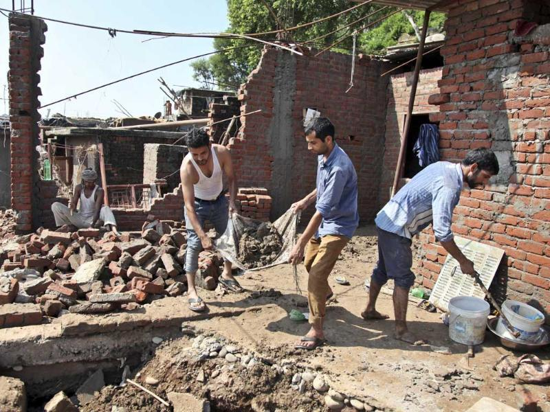 Men remove debris of their house that was damaged in floods on the banks of the Tawi River in Jammu. (AP Photo)