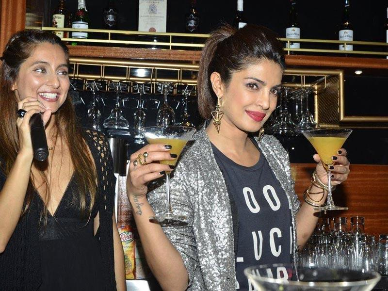 Actor Priyanka Chopra holds up cocktails prepared by her after launching her brother Siddharth Chopra's pub-lounge entitled Mugshot Lounge in Pune on September 7, 2014. (Photo: IANS)