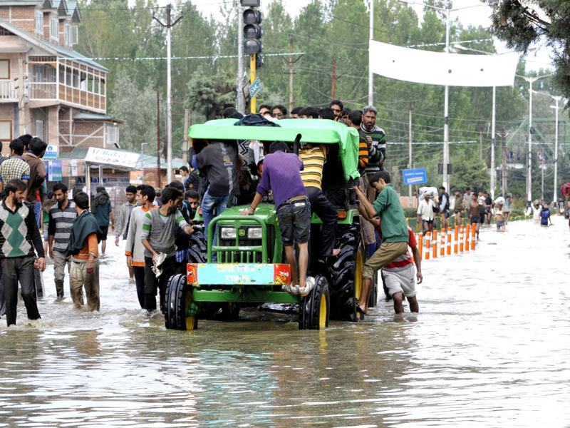 A tractor rescuing stranded people in Srinagar. (Nitin Kanotra/HT Photo)