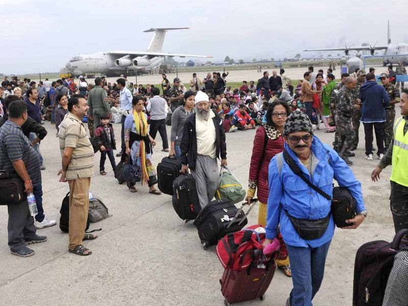 People lining up at the Srinagar airbase, waiting to be flown out in IAF planes. (Nitin Kanotra/HT Photo)