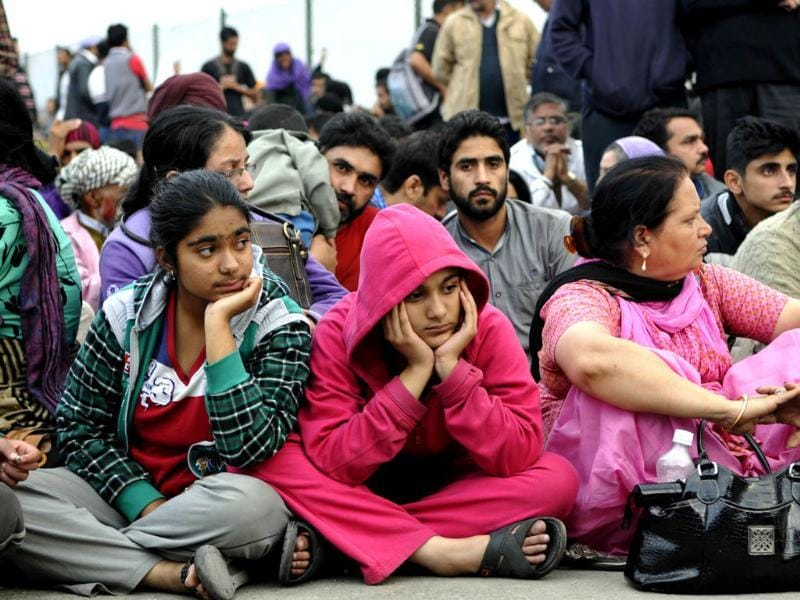 People waiting at the Srinagar airbase, waiting to be flown out in IAF planes. (Nitin Kanotra/HT Photo)