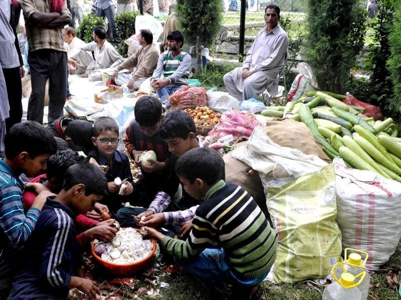 Children assist in chopping vegetables at a camp in Srinagar. (Nitin Kanotra/HT Photo)