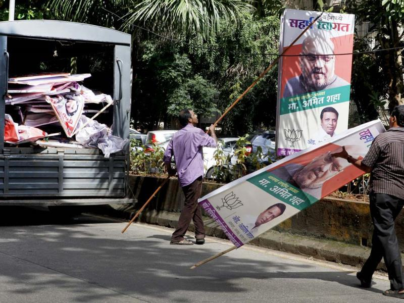 MCGM workers pull apart the banners of political parties in Bandra a day after the election code of conduct came into force for the upcoming assembly polls. (Kalpak Pathak/HT photo)