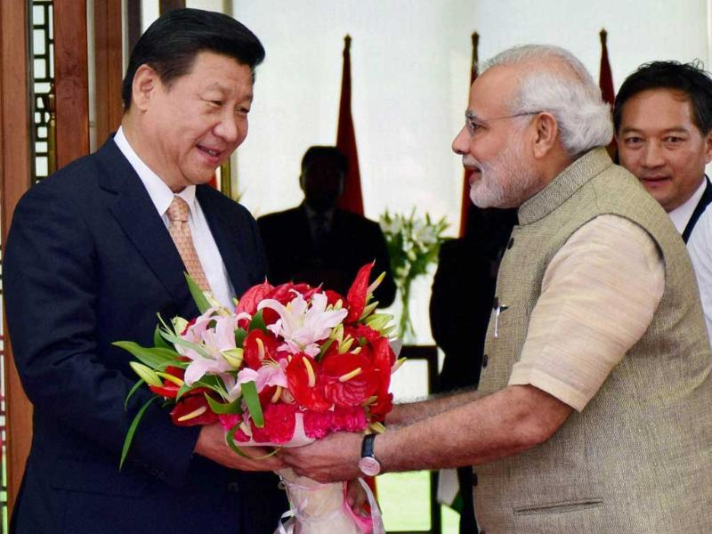 Prime Minister Narendra Modi greets Chinese President Xi Jinping upon the latter's arrival at a hotel in Ahmedabad. (PTI Photo)