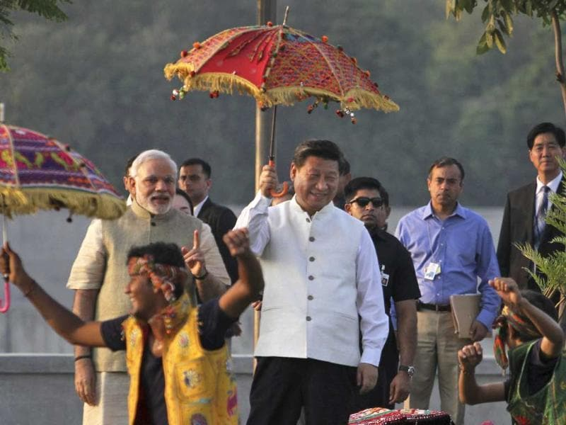Chinese President Xi Jinping holding umbrella and Narendra Modi watch a cultural performance as they walk on the Sabarmati River front in Ahmadabad.(Ajit Solanki/ AP Photo)