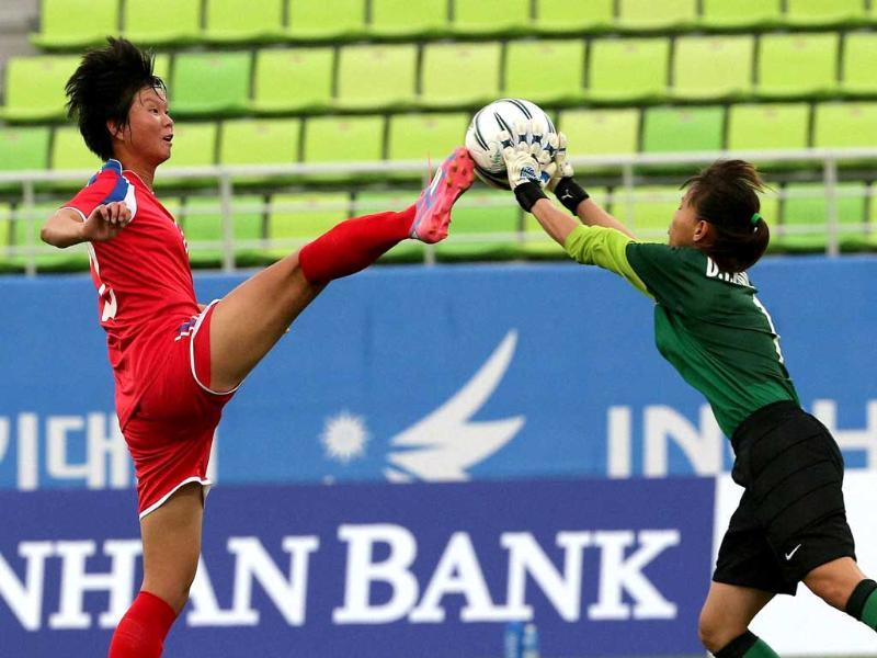 North Korea's Yunmi Kim attempts to kick the ball from Vietnam goalkeeper Thi Kieu Trinh Dang during their women's first round group C soccer match at the 17th Asian Games in Incheon, South Korea. (AP Photo)