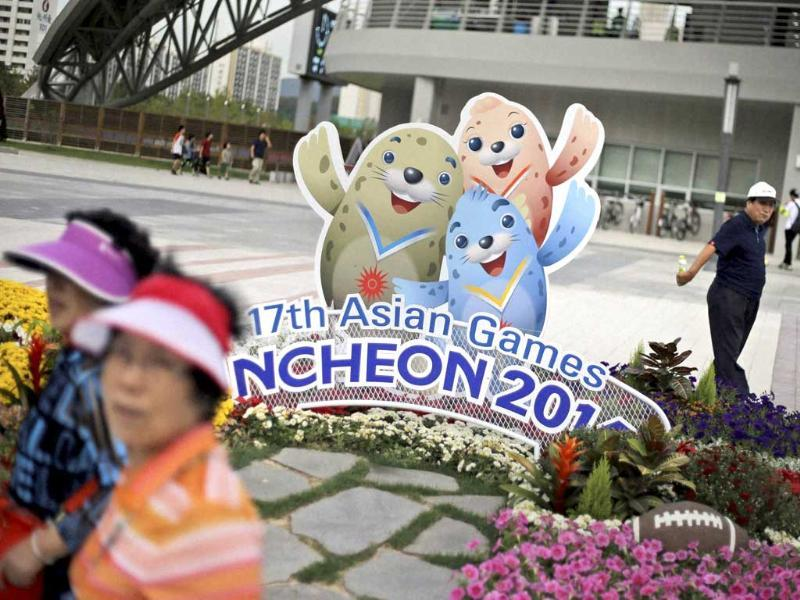 People walk past the cardboard cutouts of Barame, left, Vichuon, center, and Chumuro, the mascots of the 17th Asian Games, outside a stadium in Incheon. (AP Photo)