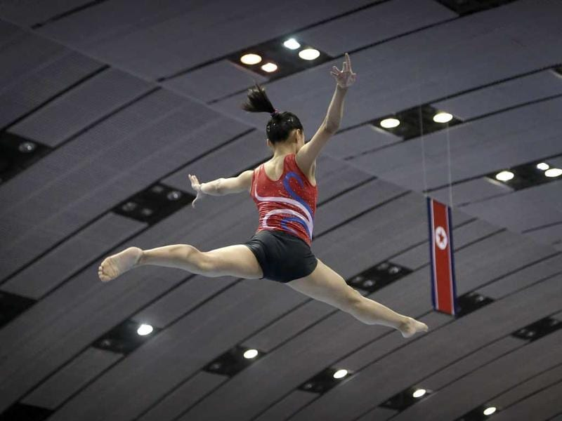 A gymnast practices her routine on the balance beam with the national flag of North Korea in the background.(AP Photo/Wong Maye-E)