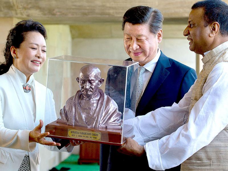 An official presents a bust of Mahatma Gandhi to Chinese President Xi Jinping and his wife Peng Liyuan during their visit to Rajghat in New Delhi on Wednesday. (AP Photo)