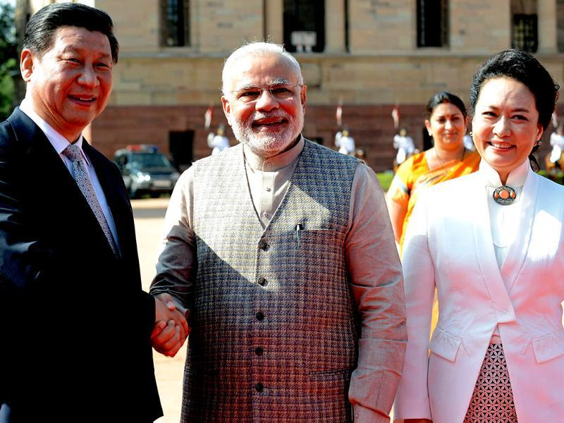 Chinese President Xi Jinping (L) shakes hands with Indian Prime Minister Narendra Modi (C) as Xi's wife Peng Liyuan looks on during a welcoming ceremony at the Presidential palace in New Delhi on Thursday. (AFP Photo)