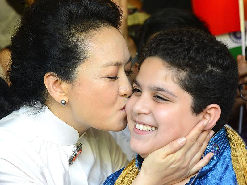 Peng Liyuan greets a child from Tagore School as she arrives for a visit in New Delhi on Thursday. (HT Photo)