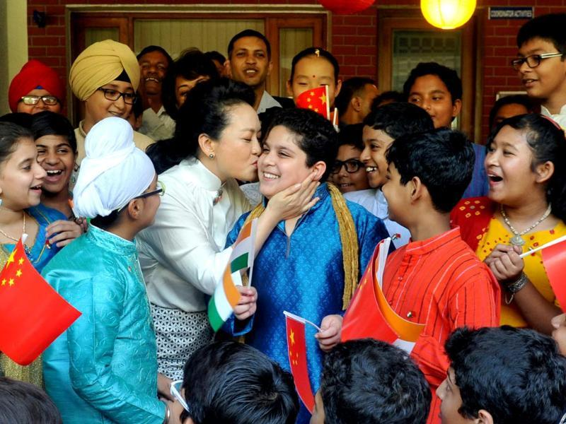 The wife of Chinese President Xi Jinping, Peng Liyuan, greets a child from the Tagore School as she arrives for a visit in New Delhi. (HT Photo)