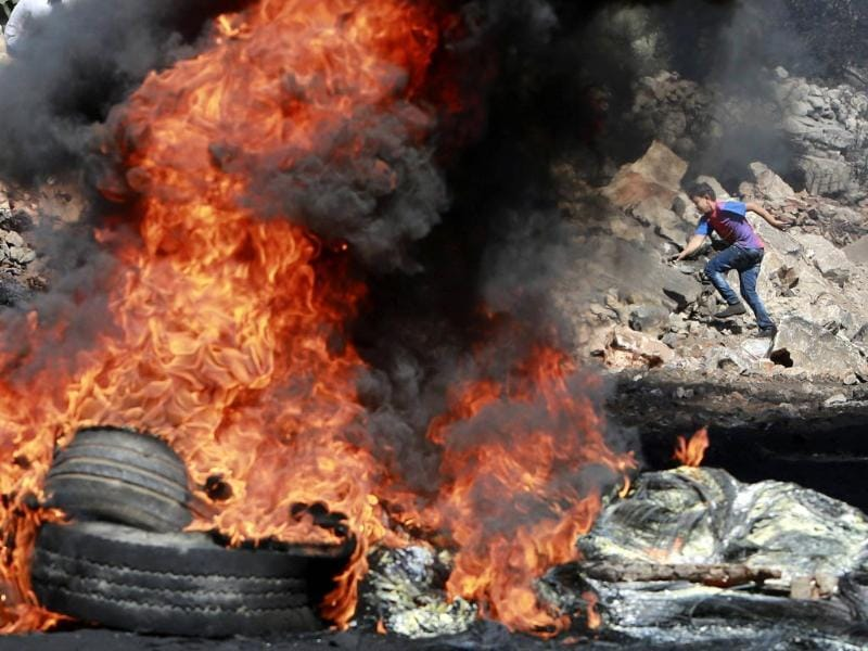 A Palestinian boy runs past burning tyres during cashes with Israeli soldiers following a protest against the near-by Jewish settlement of Qadomem, in the West Bank village of Kofr Qadom near Nablus . (Reuters)