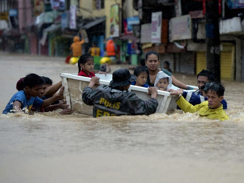 Rescuers evacuate residents after a river overflowed, flooding their homes due to heavy rains brought about by tropical storm Fung-Wong in Tumana village, Marikina City, suburban Manila. (AFP photo)