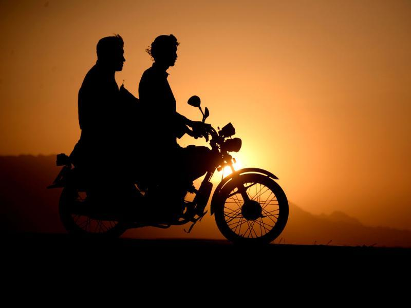 Afghan men ride on a motorcycle as the sun sets on the outskirts of Mazar-i-sharif. Afghanistan's economy has improved significantly since the fall of the Taliban regime in 2001 largely because of the infusion of international assistance. Despite significant improvement in the last decade the country is still extremely poor and remains highly dependent on foreign aid. (AFP photo)
