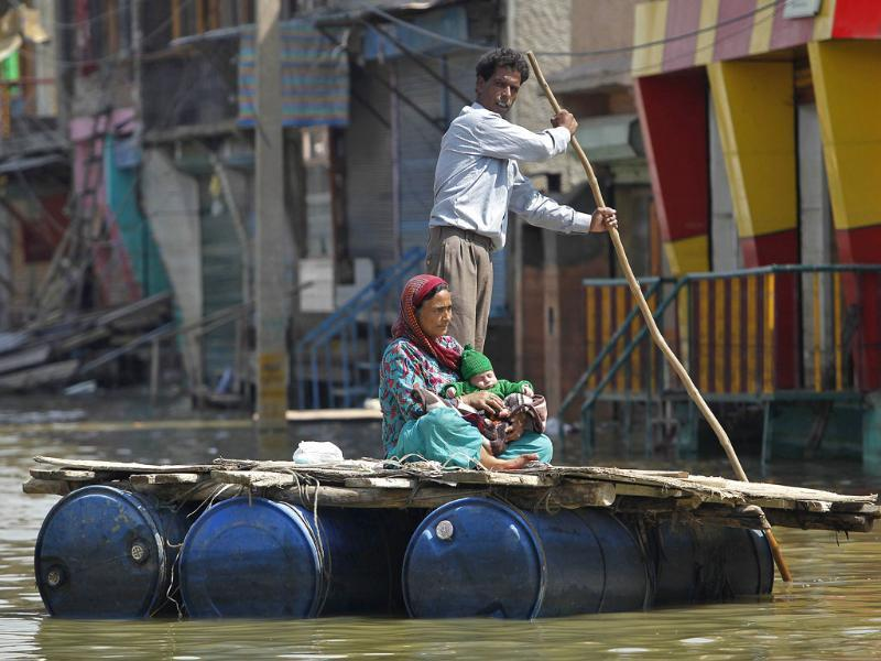 A Kashmiri man rows a makeshift raft carrying a woman and a child through the flood waters in Srinagar . (Reuters)