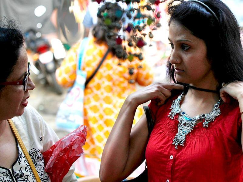 A girl tries on ornaments ahead of Navratri festival at Borivali, in Mumbai. (Vidya Subramanian/HT photo)