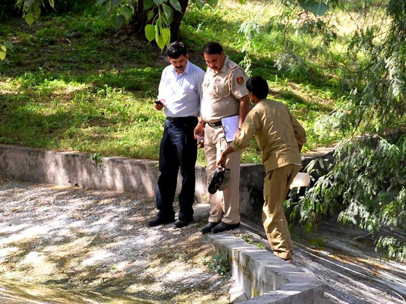 The police and zoo personnel retrieve the shoes of the schoolboy who was attacked by the white tiger at the Delhi Zoo on Tuesday. (AFP Photo)