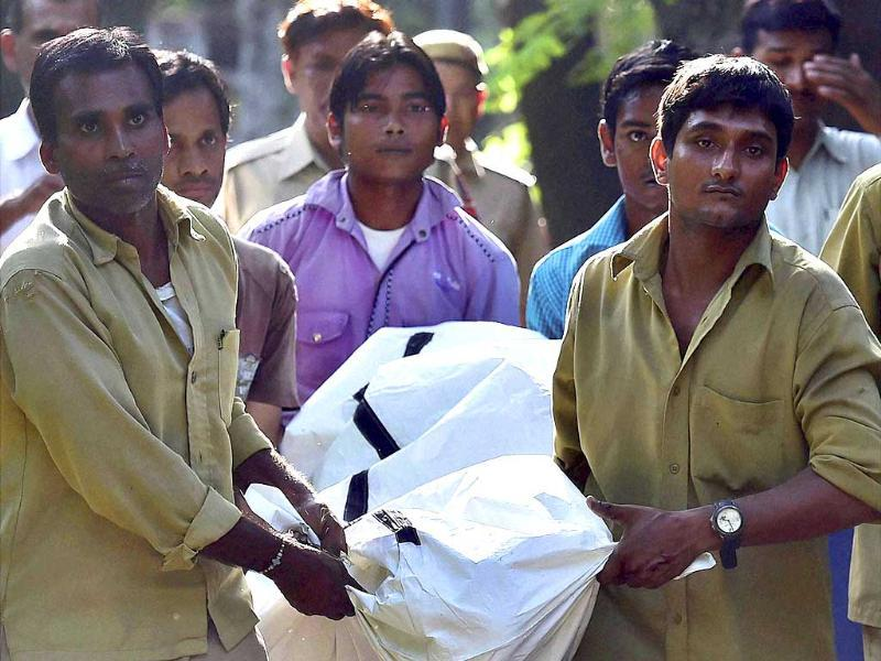 Zoo workers carry the student's dead body at the Delhi Zoo on Tuesday. (PTI Photo)