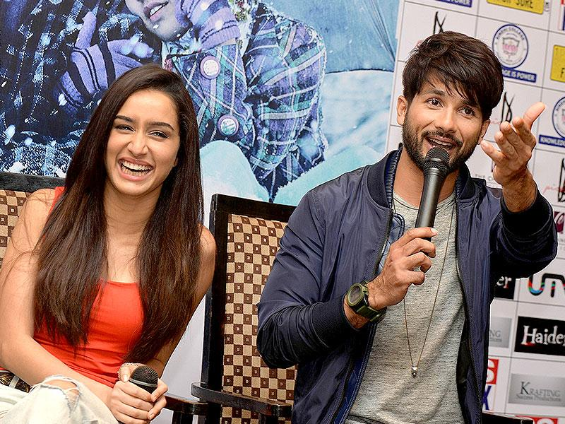Shraddha Kapoor laughs as her Haider co-actor Shahid talks to the reporters during a promotional event in Bangalore. (AFP Photo)