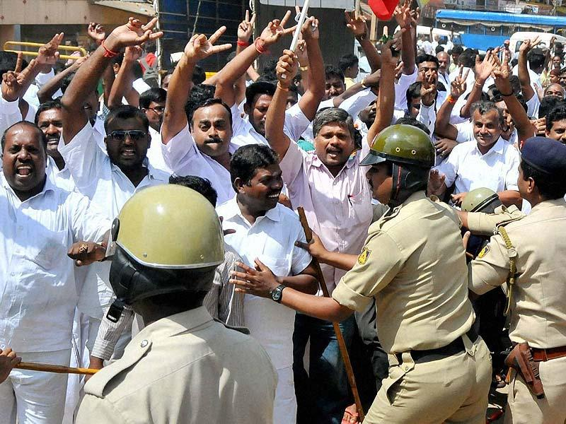 Security men push away supporters of J Jayalalithaa while she proceeds to the special court in Bangalore. (PTI photo)