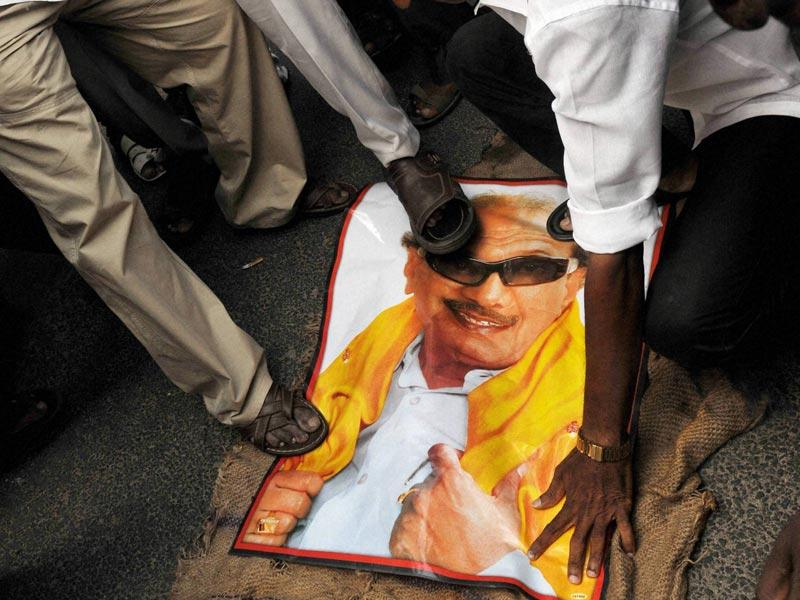Members of AIADMK stomp on a poster of DMK chief K Karunanidhi during a protest following a Bangalore special court pronouncing Tamil Nadu chief minister J Jayalalithaa guilty in a disproportionate assets case, in Coimbatore. (PTI Photo)