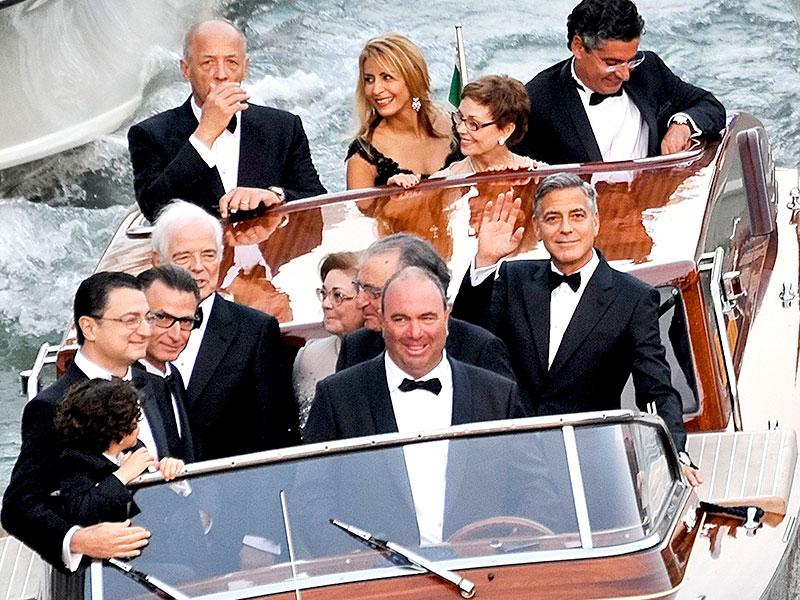 Actor George Clooney, right, waves from a boat with Ramzi Alamuddin, third from right front row, father of her fiancee Amal Alamuddin, his father Nick Clooney, fifth from right front row, and his mother Nina Bruce, second from right back row on their way to the Aman hotel ahead of his wedding in Venice, Italy. (AP)