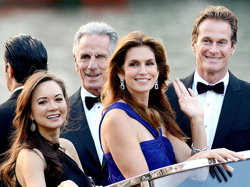 Cindy Crawford waves as hubby Rande Gerber smiles from a boat, as they go to George Clooney's wedding with Amal Alamuddin, in Venice, Italy. (AP)
