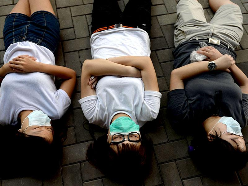 Pro-democracy demonstrators rest after a night of protesting at a rally outside the Hong Kong government headquarters. (AFP Photo)
