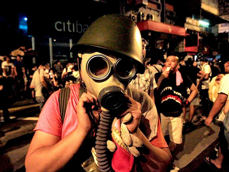 A protester puts on a gas mask to prepare for a possible tear gas attack as hundreds of protesters block a main road at Hong Kong's shopping Mongkok district. (Reuters Photo)