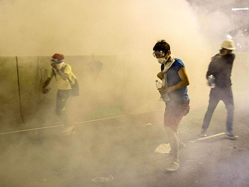 Protesters take cover from tear gas fired by police during riots that followed a pro-democracy protest in Hong Kong. (AFP Photo)
