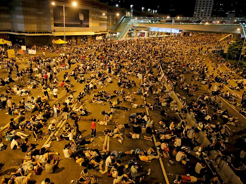 Protesters take rest at a main road in the financial central district after riot police use tear gas against them as thousands of people blocked the road in Hong Kong. (AP Photo)