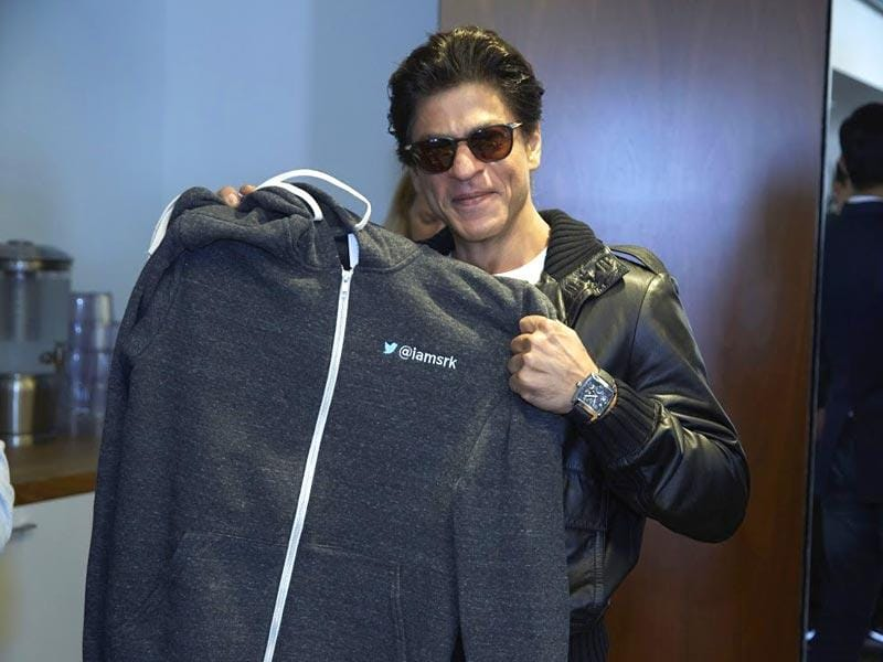 Shah Rukh holds up the customised hoodie presented by Twitter to him.