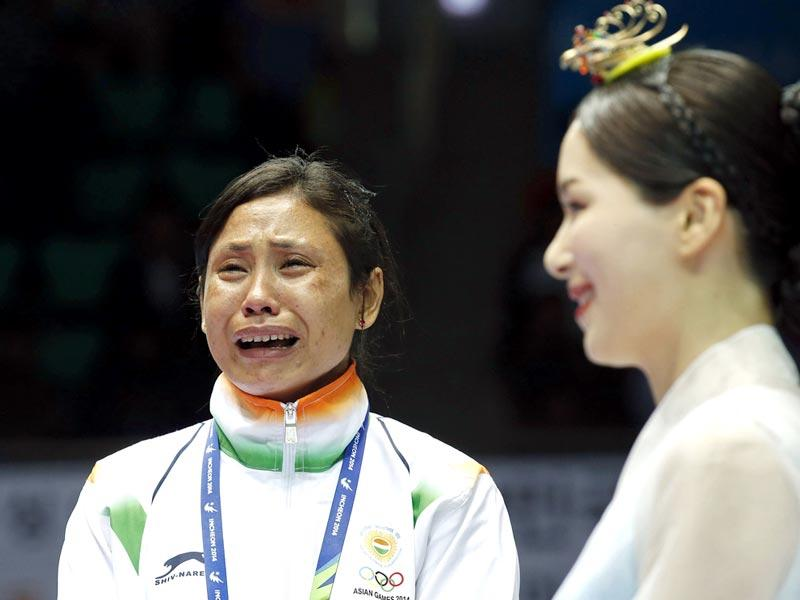 Sarita Devi cries at the podium after refusing to accept the bronze medal during the award ceremony of lightweight category boxing event. (PTI Photo)