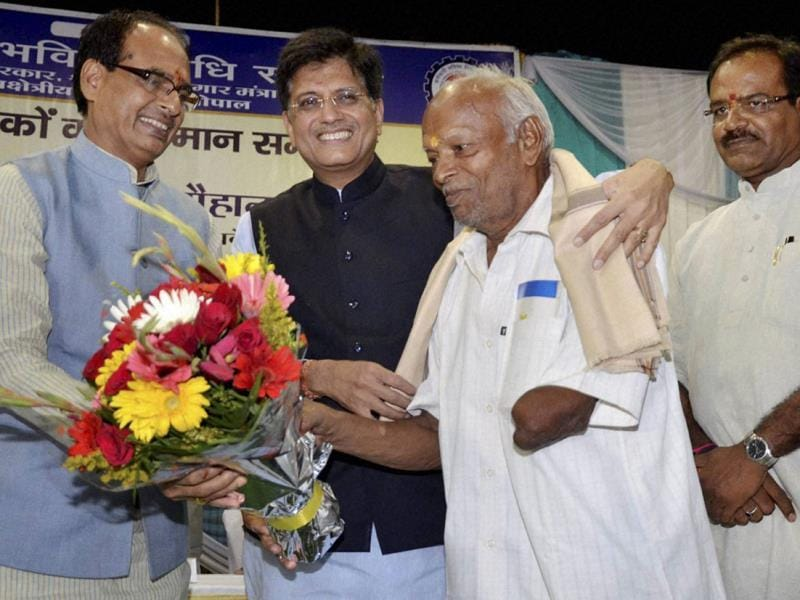 MP chief minister Shivraj Singh Chouhan with union minister Piyush Goyal felicitating a beneficiary of EPFO's new pension scheme, in Bhopal on Tuesday. (PTI photo)