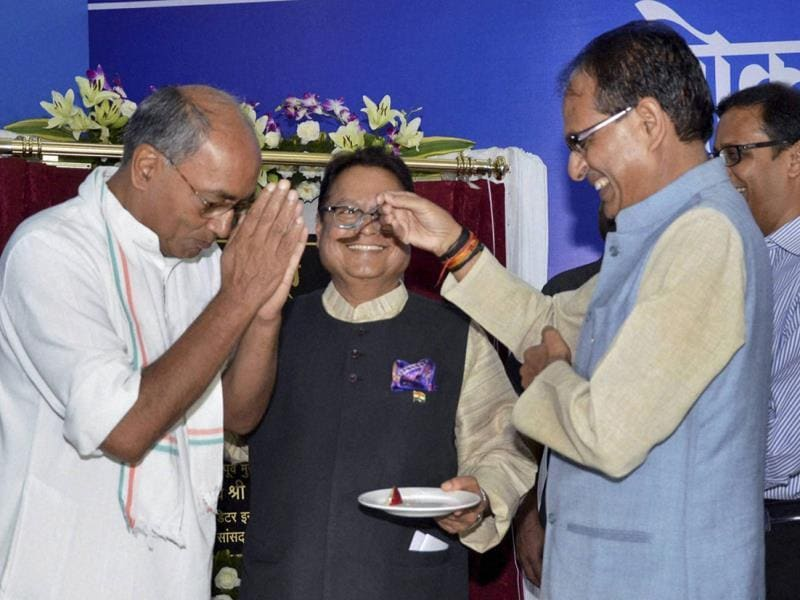 MP chief minister Shivraj Singh Chouhan offers cake to AICC general secretary Digvijay Singh at the inaugural ceremony of Lokmat Bhawan, in Bhopal on Wednesday. (PTI photo)
