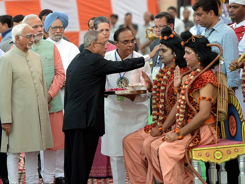 President Pranab Mukherjee applying 'Tilak' to artists, enacting Lord Ram and Laxman during Dussehra celebrations at Subhash Maidan in New Delhi. (PTI Photo)