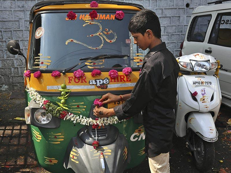 A boy decorates his auto rickshaw as he prepares to offer prayers on Vijayadasami festival in Hyderabad.(AP Photo)