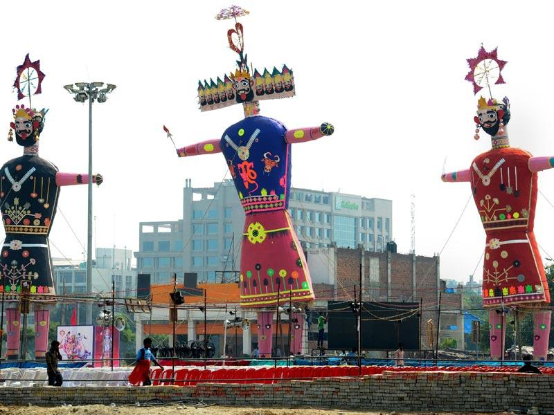 Workers walk past effigies of demon king Ravana and his son Meghnath and brother Kumbhkaran installed on the occasion of the Dussehra festival in Amritsar. (AFP Photo)