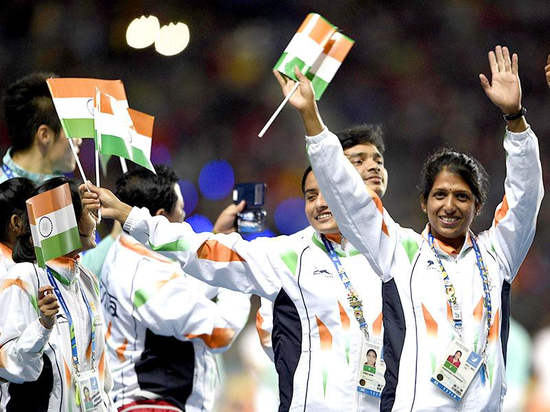 Indian athletes Annu Rani and Narayana Sharadha wave national flags as they enter the arena during the closing ceremony. (AFP Photo)