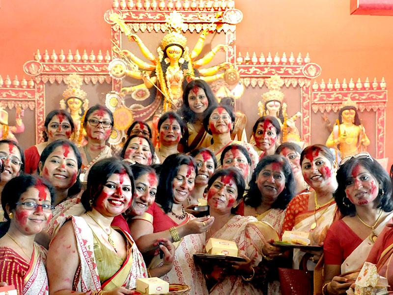 Women smearing the vermilion on each other's faces during 'Sindoor-Khela' before immersion of goddess Durga's idol in sector-14 community center, in Gurgaon. (Parveen Kumar/HT Photo)
