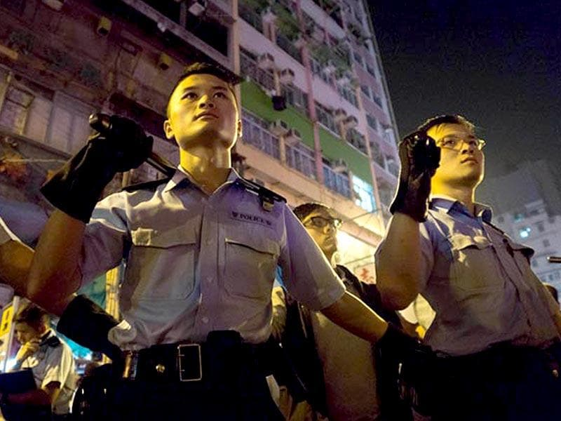 Police armed with batons stand guard in Mongkok, Hong Kong. (AFP photo)