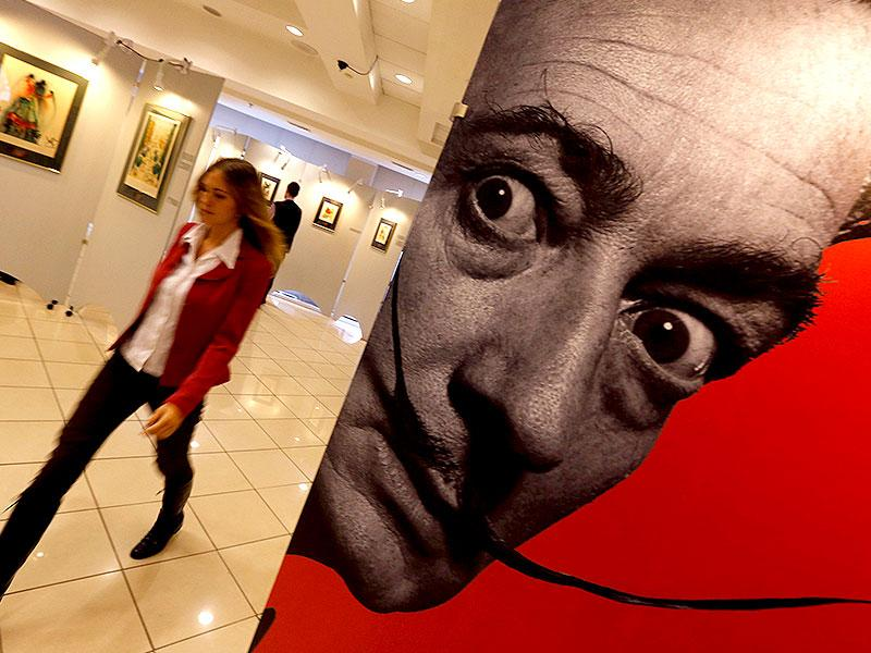 A visitor walks past a portrait of Salvador Dali during the exhibition